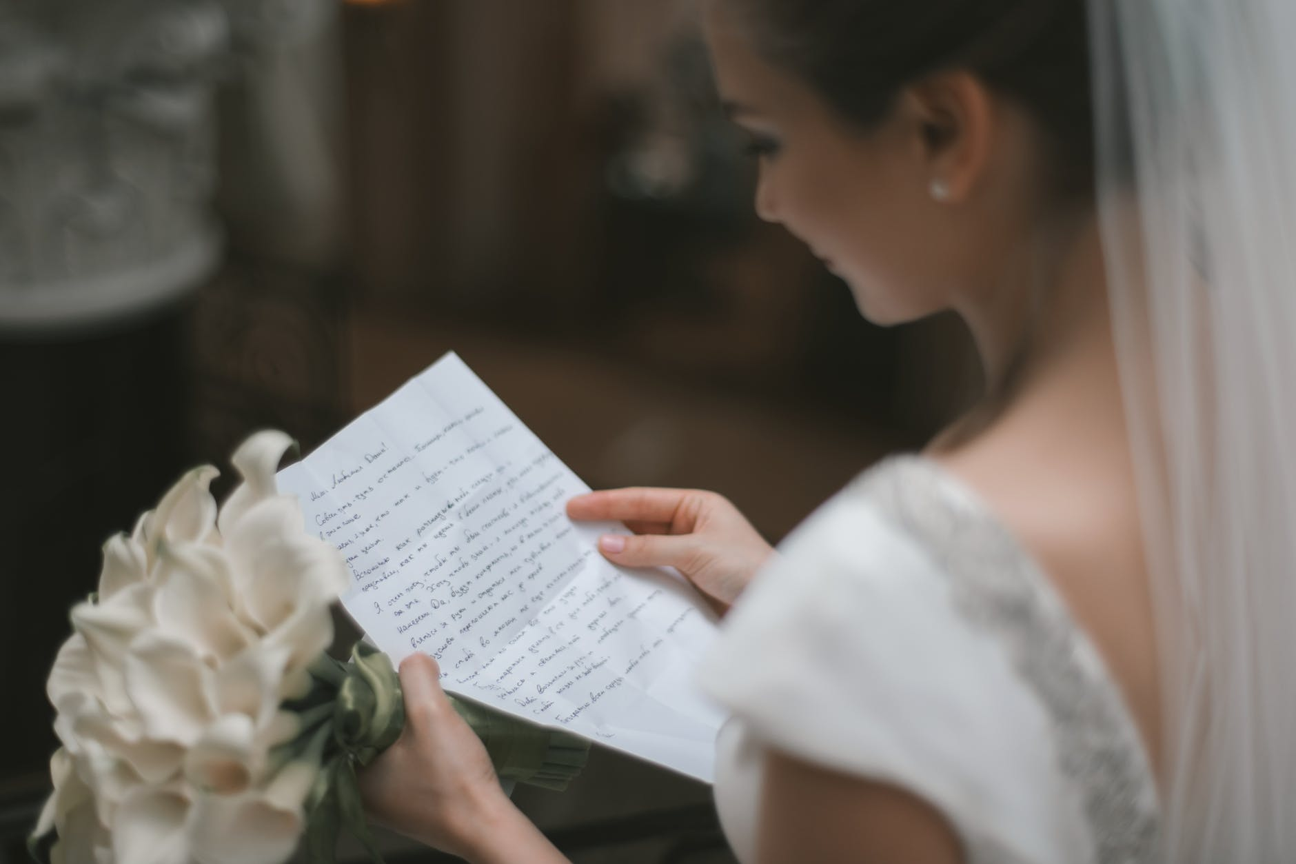 bride with bouquet and wedding vow in hands